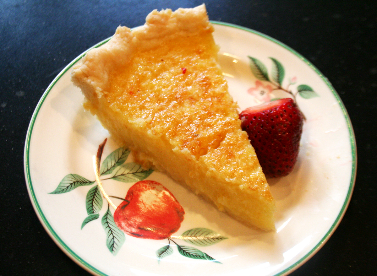 A slice of lemon chess pie, serve with fresh strawberries