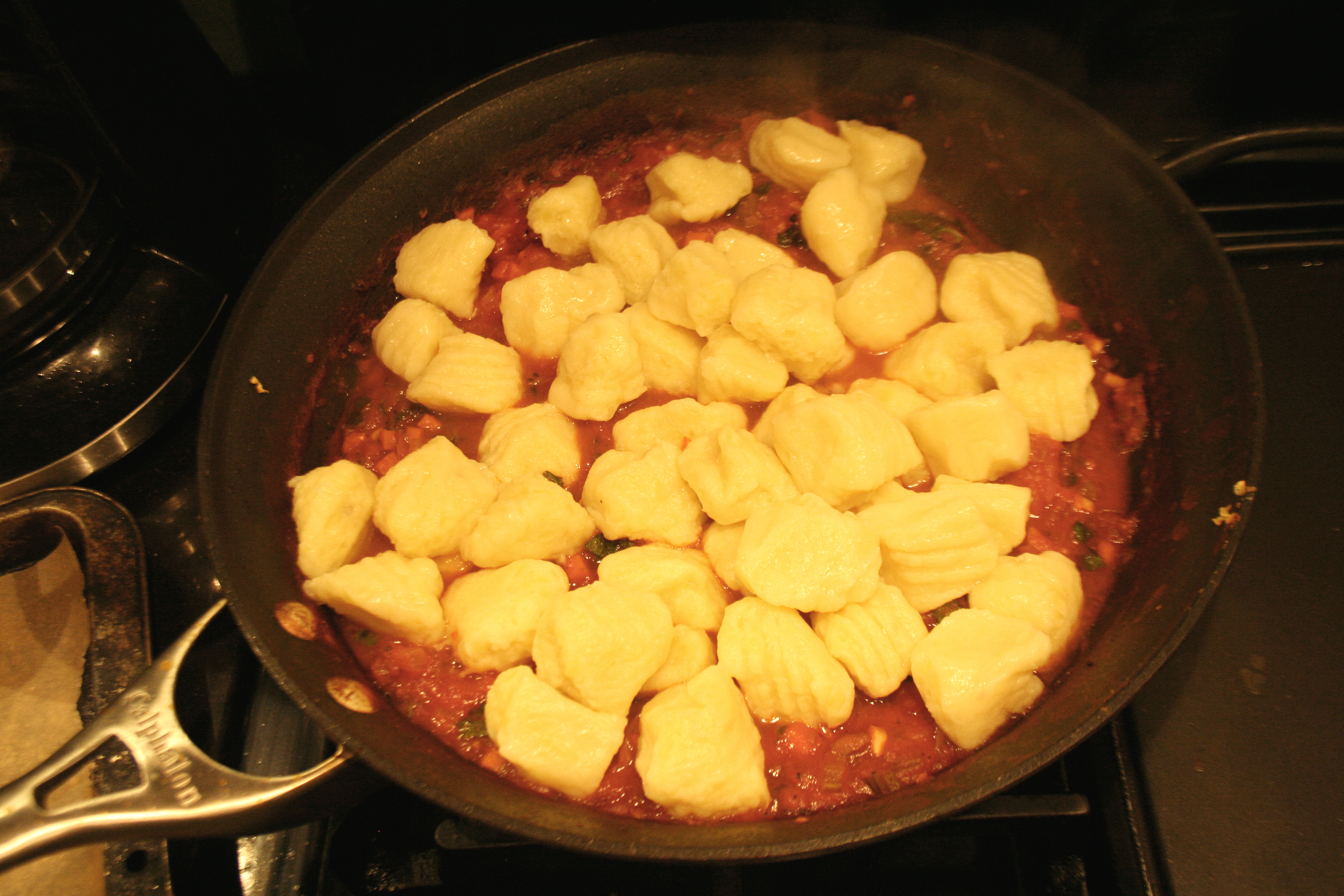 Cooked potato gnocchi tossed into the tomato sauce pan