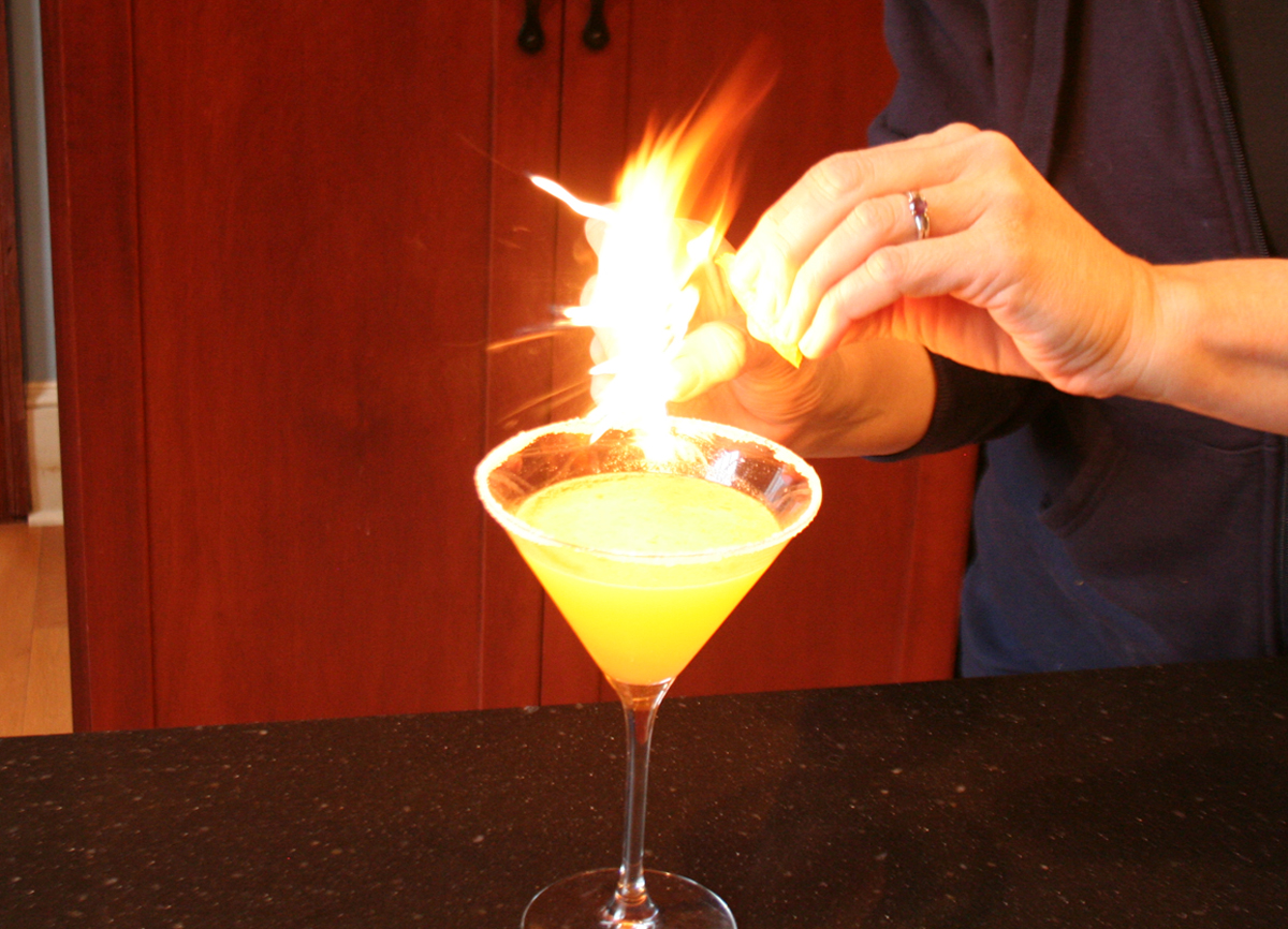 Flaming the Orange Peel over a Tangerine Drop Martini